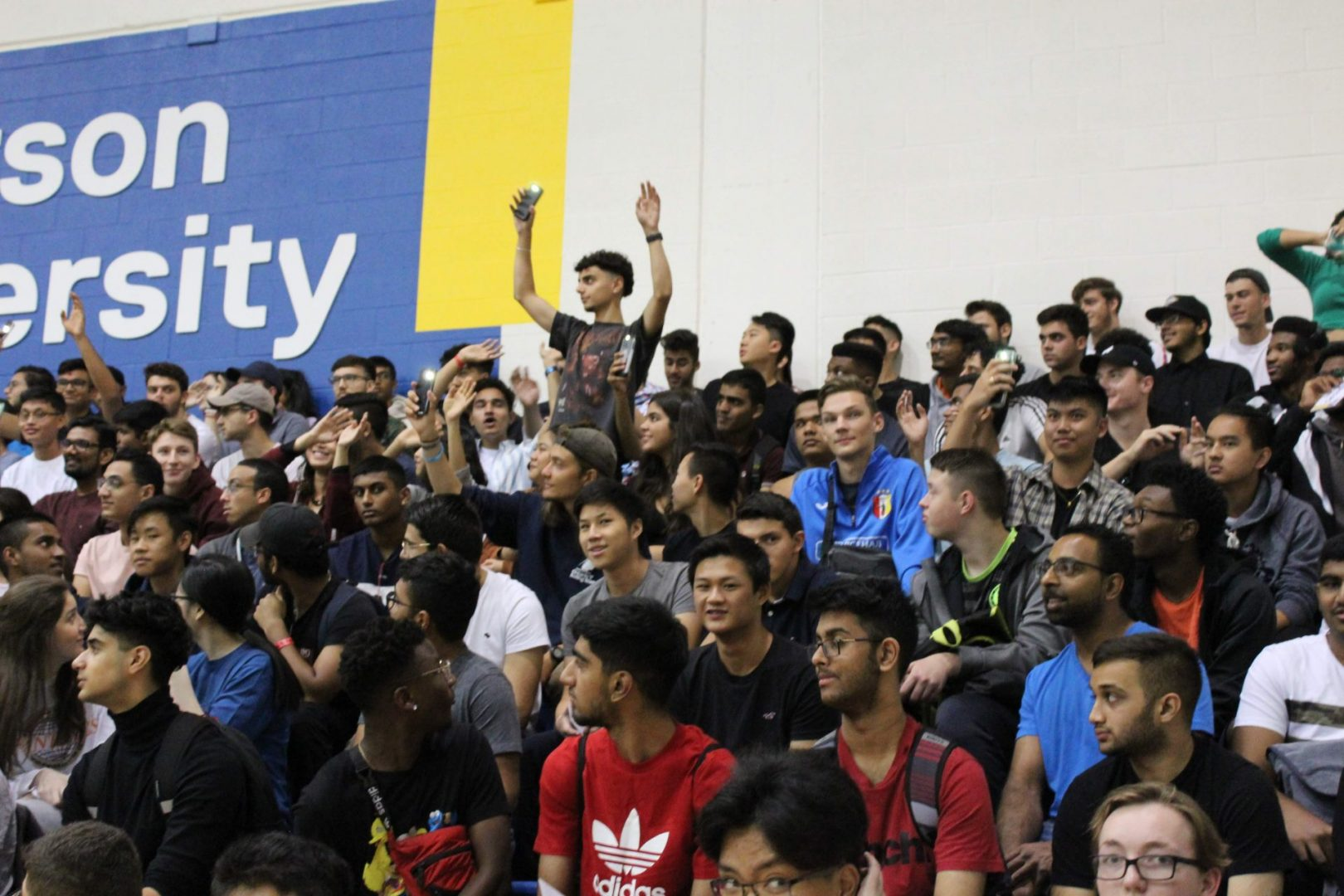 Group of students sitting while one student stands with hands in air