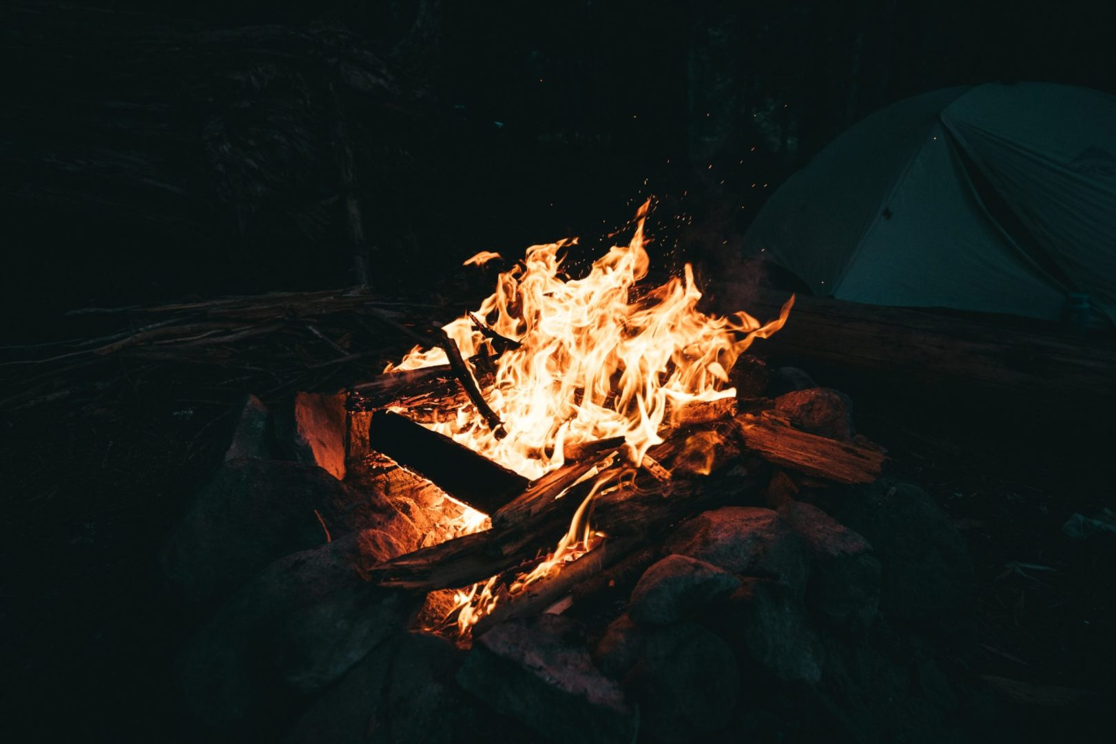 Fire burning with tent in background at night